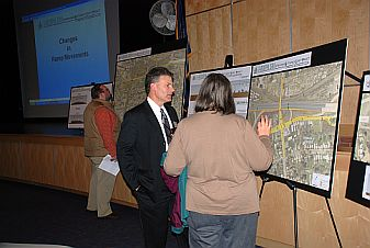 Staff member discusses with resident in front of printed out poster with map
