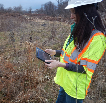 A field technician in a yellow safety vest and hard hat holding an eletronic tablet